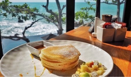 table overlooking water with a plate of pancakes